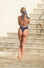 Kimberley Garner Shows off her incredible figure in a plunging swimsuit as she tops up her tan in Antibes