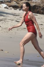 Minnie Driver In a red one-piece swimsuit for a dip in the ocean on a hot day in Malibu