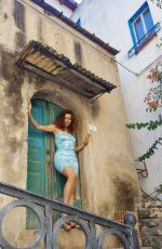 Blanca Blanco Dons a short tie-dye dress while exploring the streets of Sicily