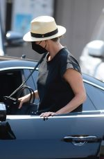 Charlize Theron Keeps it simple in a black top paired with blue jeans, sandals and a fedora for a lunch outing in Los Angeles