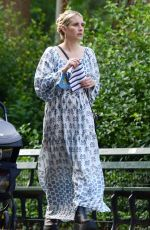 Emma Roberts In a long patterned dress and high platform boots while on a solo stroll in New York City