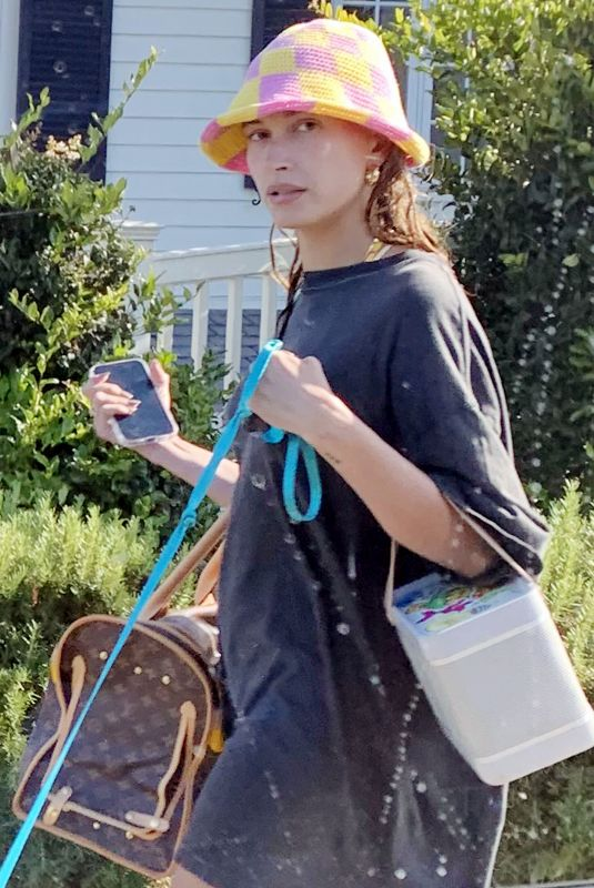 Hailey Bieber (Baldwin) Cools off in a tiny shirt dress, sandals and a funky hat after hitting the beach in Santa Barbara