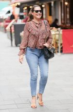 Kelly Brook Flashes peachy posterior in tight denim and floral blouse at Heart radio in London