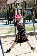Phoebe Price Wearing a black fishnet outfit and posing around the park on Monday in Los Angeles