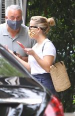 Reese Witherspoon Checks her phone messages while exiting the Bel Air Hotel