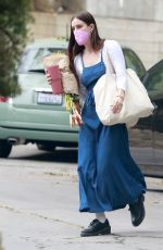 Scout Willis Wears a long denim dress with black leather shoes as she arrives with a bouquet of flowers at a friend