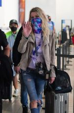 Tara Reid Waves at the camera as she arrives in good spirits with friends at LAX in Los Angeles