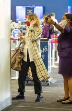 Elizabeth Olsen Taking directions from staff ahead of a flight out of Los Angeles