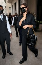 Irina Shayk Wearing pinstriped dress pants and a matching top as she leaves her hotel in Milan, Italy