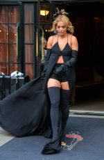 Rita Ora Wore a revealing black cape with black shorts and knee high black boots in New York