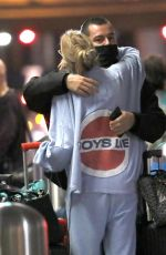 """Stella Maxwell Wears a """"Boys Lie"""" jacket while hugging an unidentified boy at the airport in Los Angeles"""
