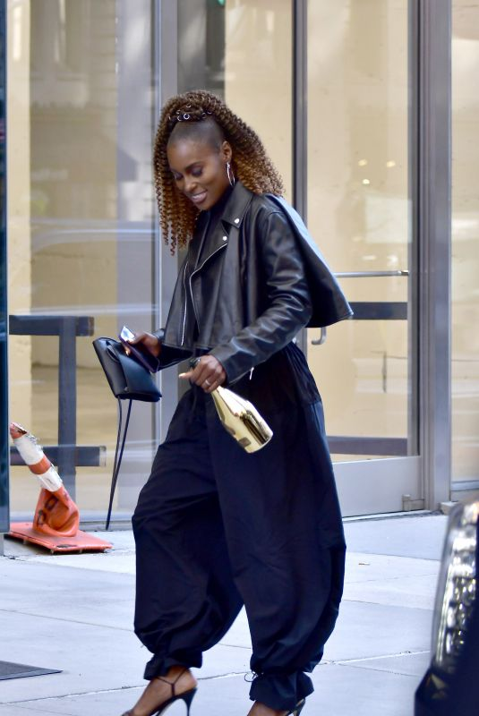 Issa Rae Holds an open bottle of champagne while heading to an office building in New York